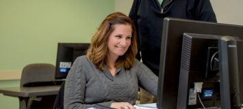 A woman smiles at a camera