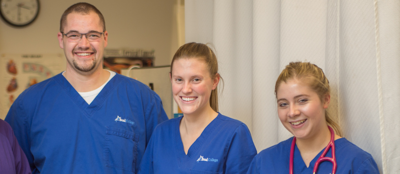 three Beal medical students wearing blue scrubs smiling at the camera