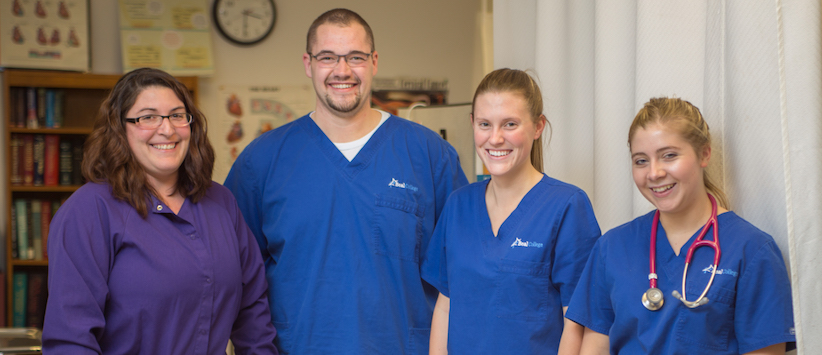A group of healthcare students and an instructor smiling at the camera. If you're looking for Healthcare Professional Programs in Bangor, Maine call Beal.