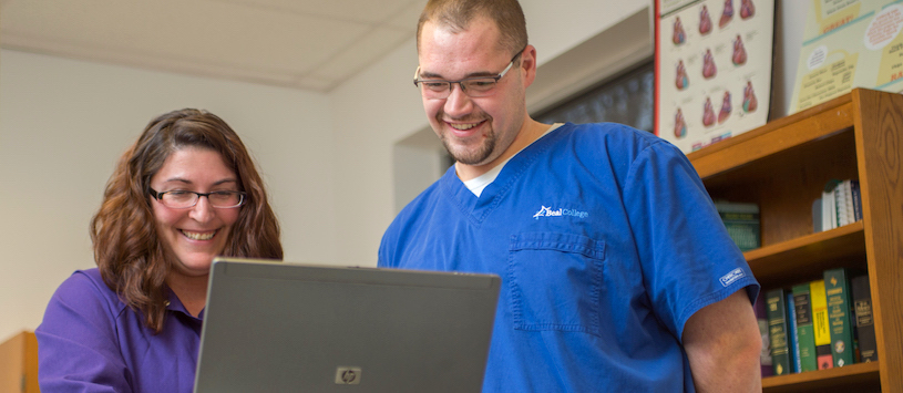 A HIT student and instructor look at a computer screen. If you want to find a Health Information Technology Program call Beal College.