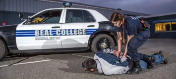 A female law enforcement student practising making an arrest