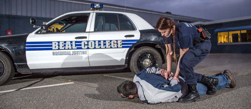 A female law enforcement student practising making an arrest. If you want to get your law enforcement degree in Bangor, ME then call Beal College today!