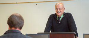 A elderly man teaches students