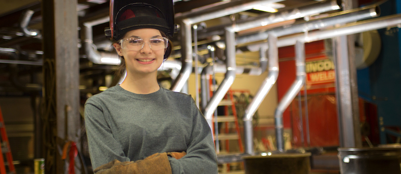 A female Beal College welding student wearing glasses with arms folded. She is smiling at the camera. Take professional career training programs at Beal!