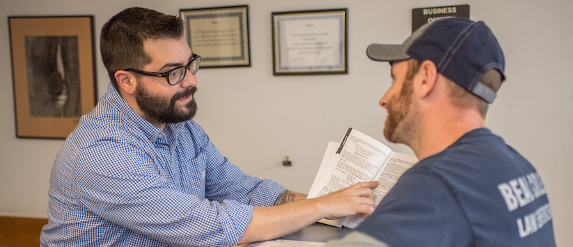 A man showing a student a program page.
