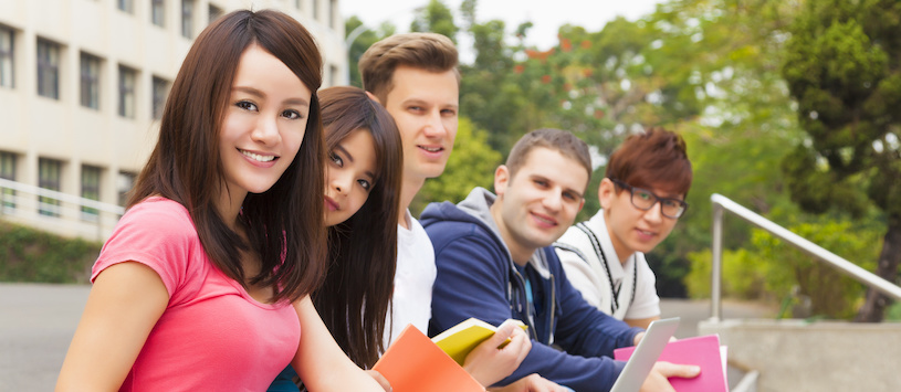 A group of students sitting outside smiling