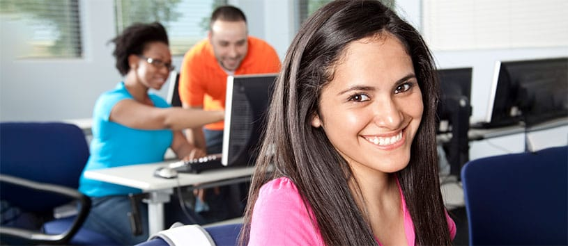 Smiling woman sitting in a computer lab.