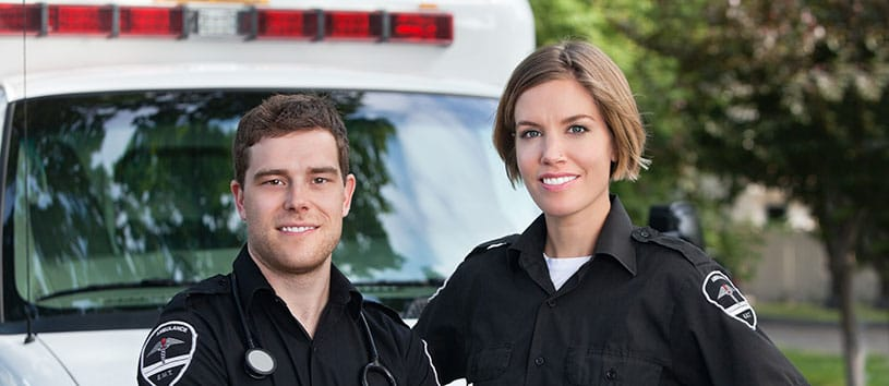 Two Emergency Medical Services students stand in front of an ambulance