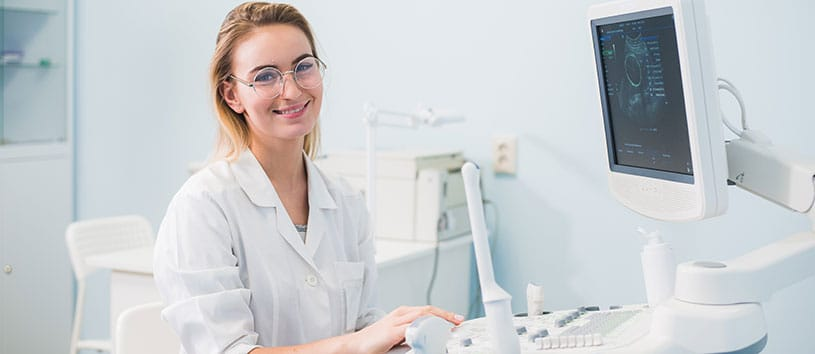 A Health and Science professional sits at a monitor with a variety of medical instruments around her.