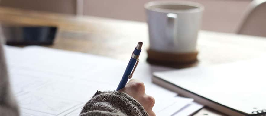 Closeup of a person writing with a pen on paper.